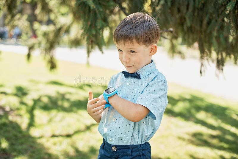 Little boy talking on smart watch with mother stock images