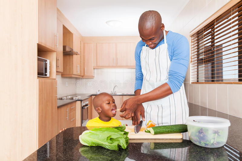 Little boy tasting tomato. While his father cooking in kitchen at home stock photography