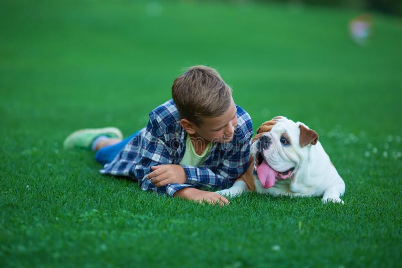 Little boy teenager with his dog bulldog in park on a sunny day on green grass park land enjoy life together with his friend.  stock photo