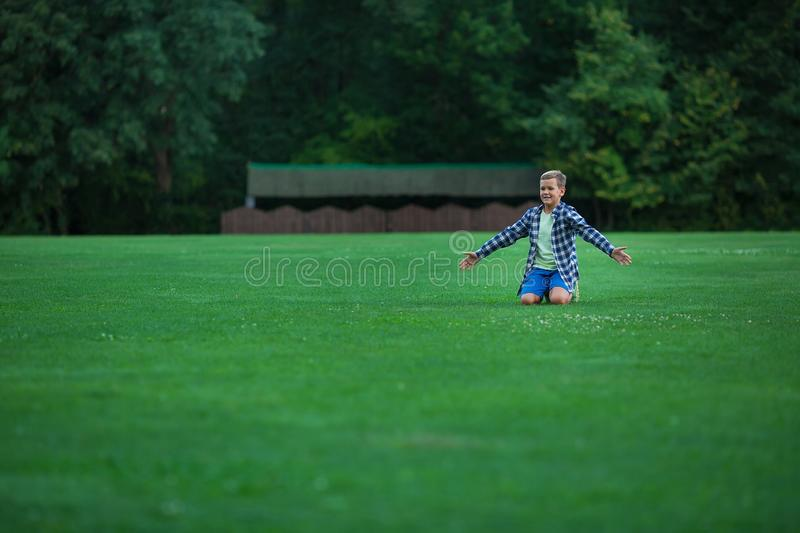 Little boy teenager with his dog bulldog in park on a sunny day on green grass park land enjoy life together with his friend.  royalty free stock photo