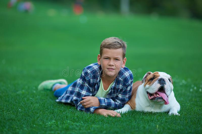 Little boy teenager with his dog bulldog in park on a sunny day on green grass park land enjoy life together with his friend.  stock image