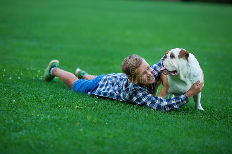 Little boy teenager with his dog bulldog in park on a sunny day on green grass park land enjoy life together with his friend.  royalty free stock photos