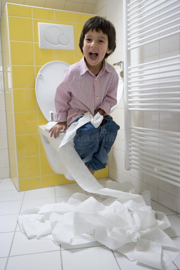 Little Boy tem muito divertimento com Toalete-papel dentro fotos de stock royalty free