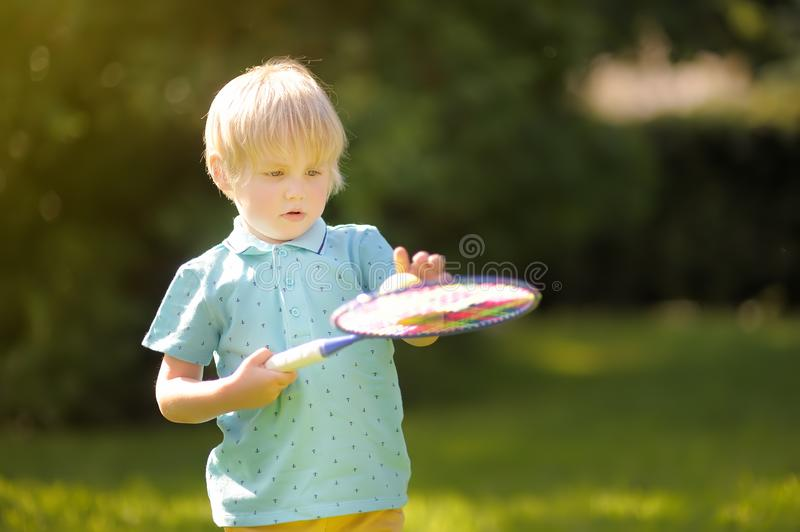 Little boy during tennis training or workout. Preschooler playing badminton in summer park. Child with small tennis racket and royalty free stock photo