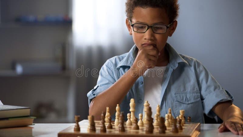 Little boy thinking on chess move, intelligent hobby, logic development, leisure. Stock photo royalty free stock photography