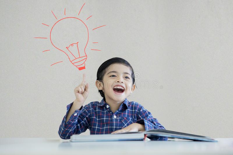 Little boy thinking an idea under a light bulb. Picture of little boy reading book while thinking an idea and sitting under a drawn light bulb background royalty free stock photos