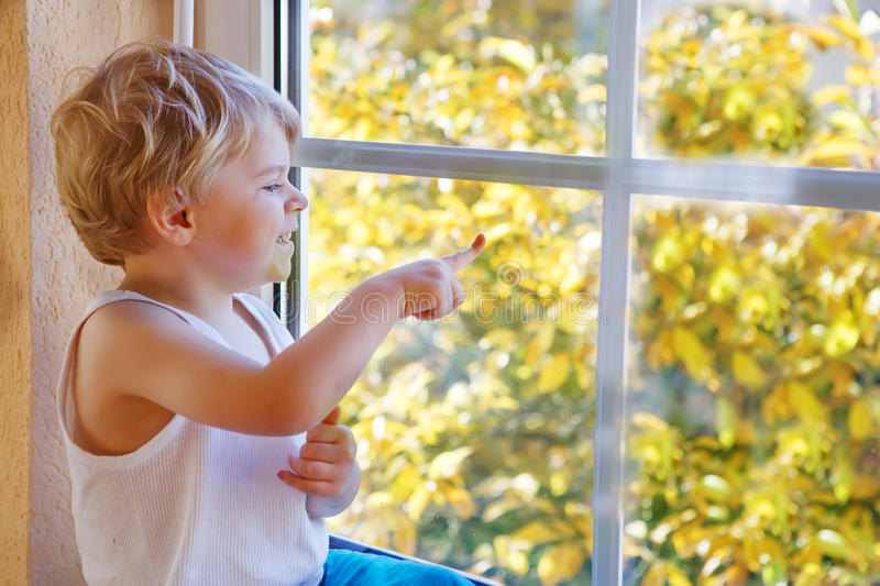 Little boy of three years looking out of the window royalty free stock photo
