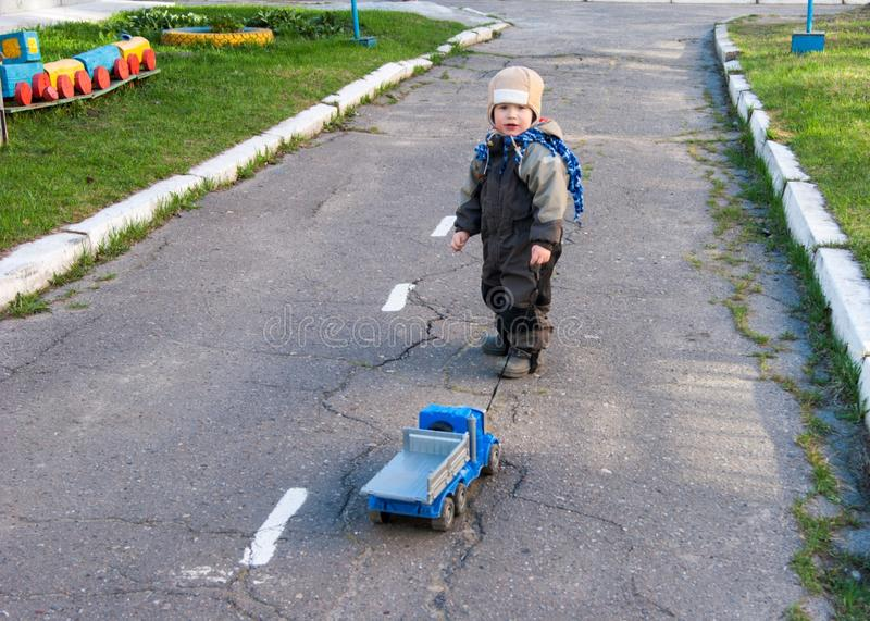 A little boy of three years old is playing around the kindergarten with his toy truck royalty free stock photos