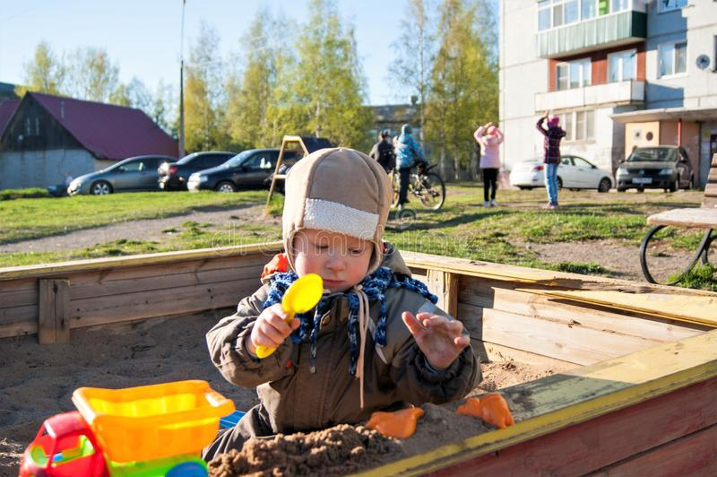 A little boy of three years old is playing on a cool spring sunny day in the sandbox in the city yard with his toy truck stock photo