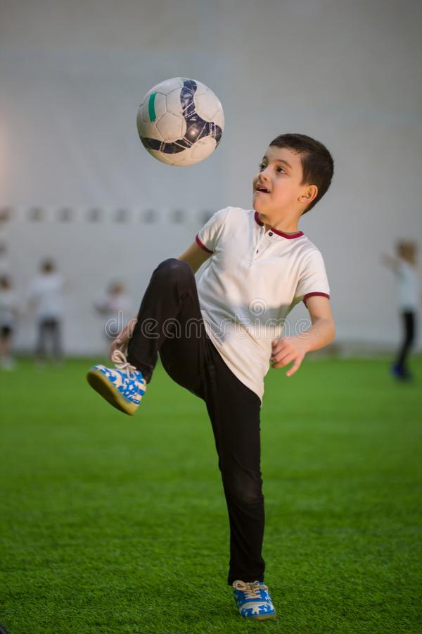 A little boy throwing ball on the field playing football with other kids stock image