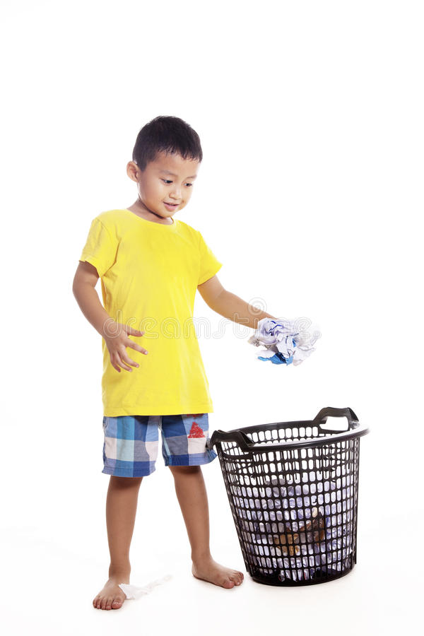 Little boy throwing waste paper. Responsibility of young little boy to keep clean environment by throwing waste paper to recycle bin royalty free stock image