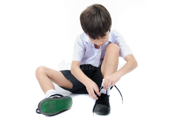 Little boy tie shoes ready for school on white background. Isolate royalty free stock images