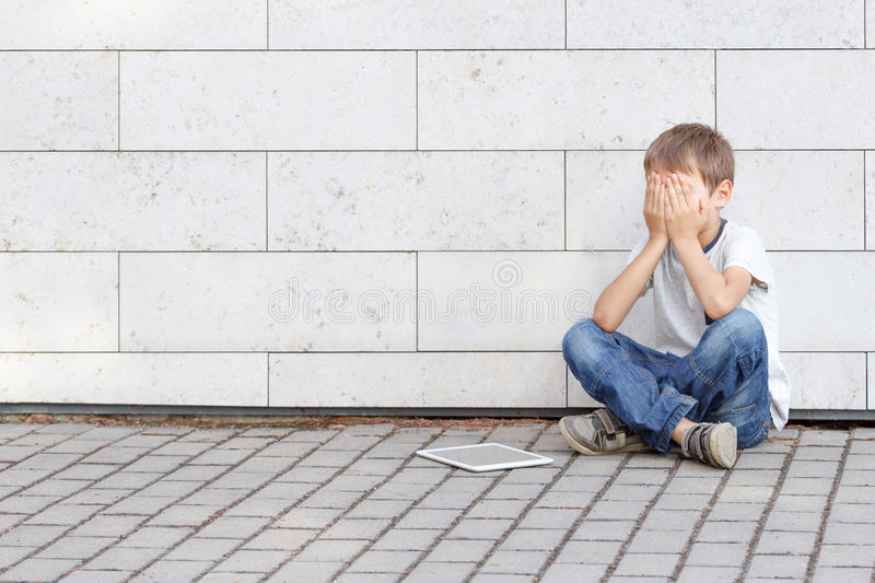 Little boy tired sad and stressed with tablet computer PC. Kid sitting on the ground, holding his head, close eyes stock photography