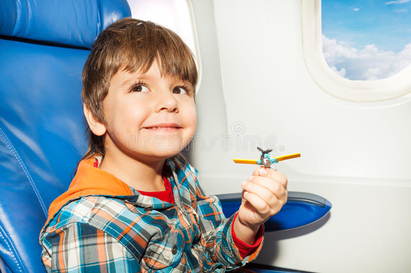 Little boy with toy plane fly in airplane. Little boy fly in airplane and playing with toy plastic plane looking at camera stock image