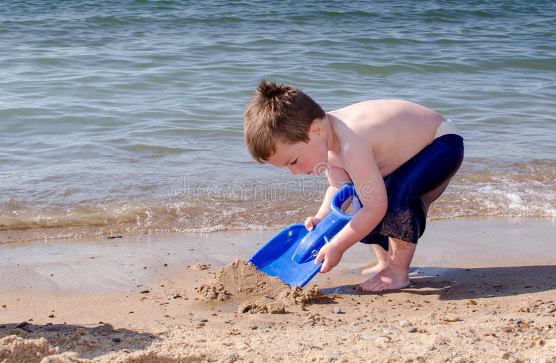 Little boy with toy shovel on the beach royalty free stock photography