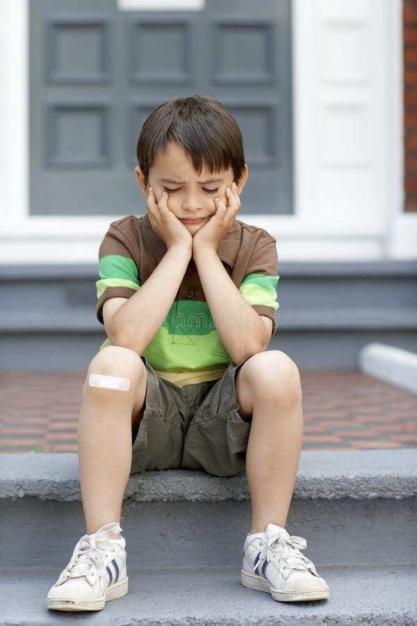 Little Boy triste que senta-se em etapas imagem de stock