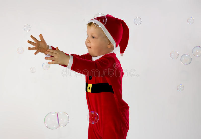 Little boy trying to catch some soap bubbles royalty free stock photography