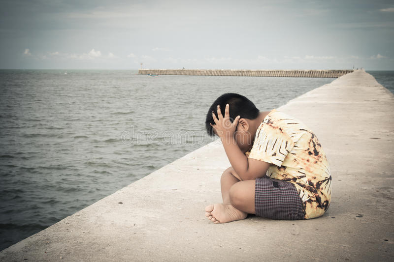 Little boy unhappy sitting alone on bridge royalty free stock images