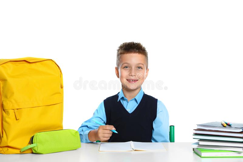 Little boy in uniform doing  at desk against white background. School stationery royalty free stock photography