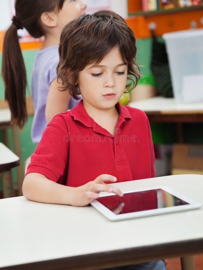 Little Boy unter Verwendung Digital-Tablets im Kindergarten lizenzfreie stockbilder