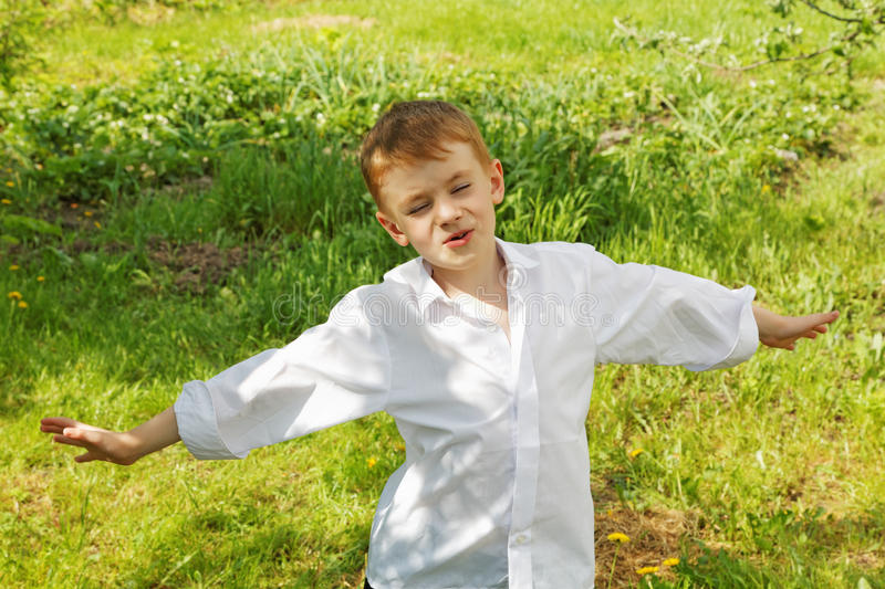The little boy unties a tie against green stock image