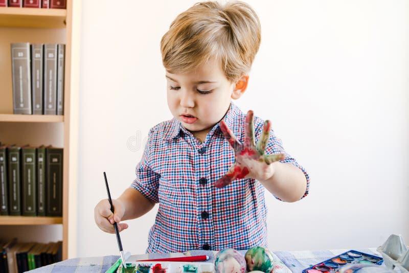 Little Boy usando cores de água para pintar em casa fotos de stock royalty free