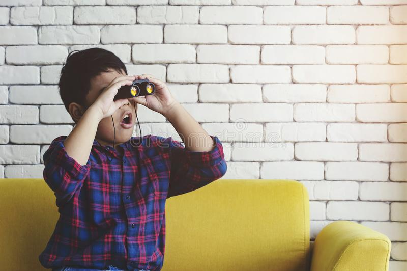 Little boy using binoculars in the living room stock image