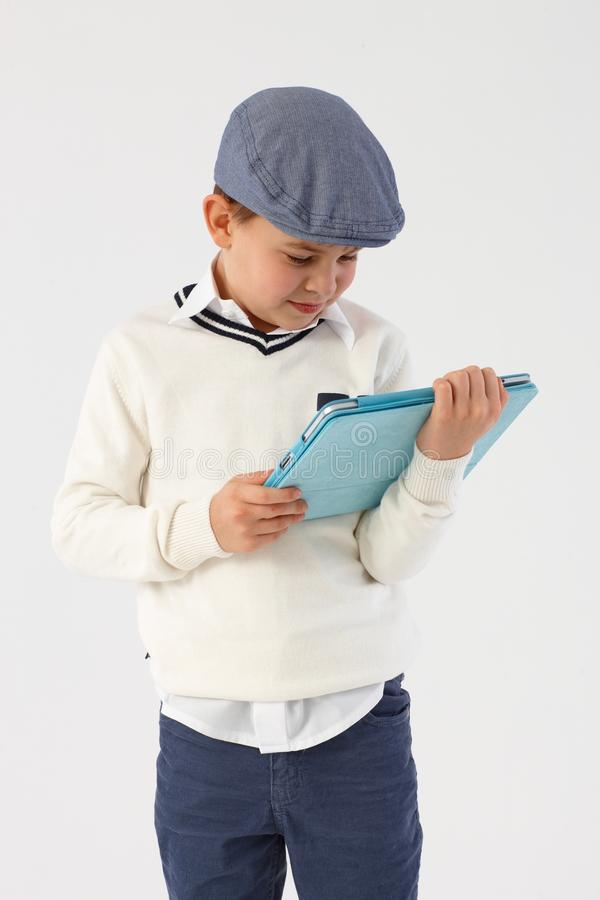 Little boy using tablet computer. Little boy in cool hat using tablet pc royalty free stock photos