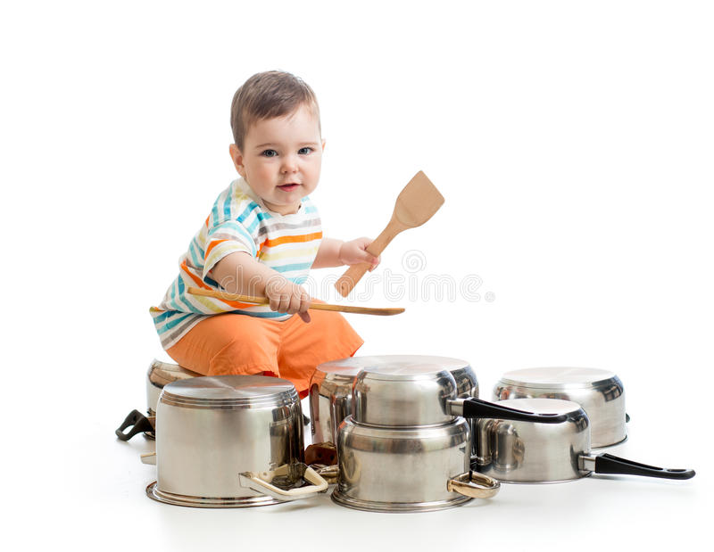 Little boy using wooden spoons to bang pans drumset. Young boy using wooden spoons to bang pans drumset royalty free stock photos