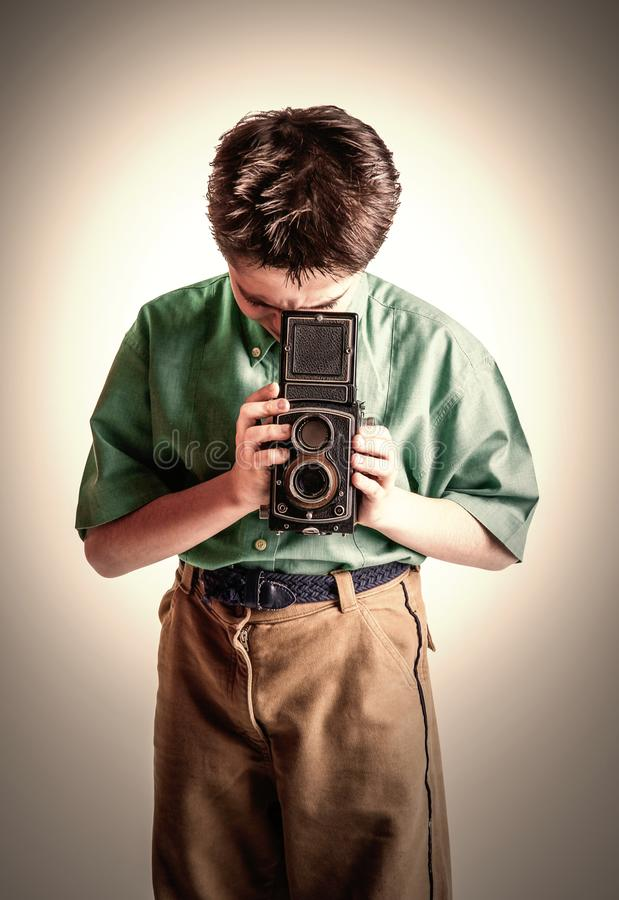Little boy with a vintage camera stock image
