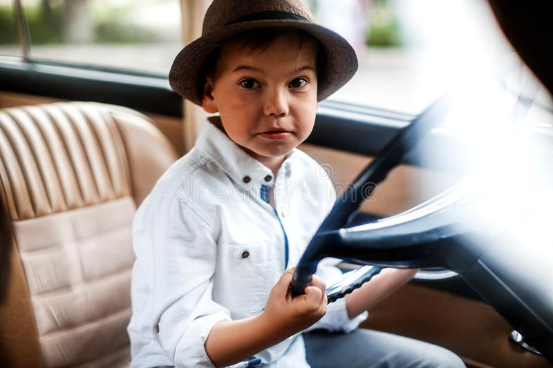 Little boy in vintage clothes stands near the retro car. Time machine stock photo