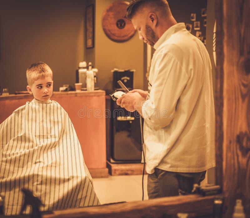Little boy visiting hairstylist stock photo