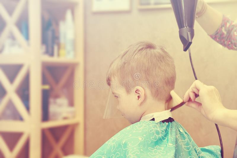 Little boy visiting hairstylist in barber shop stock photos