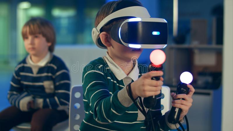 Little boy in vr headset playing virtual reality game with controllers while another boy waiting for his turn royalty free stock photo