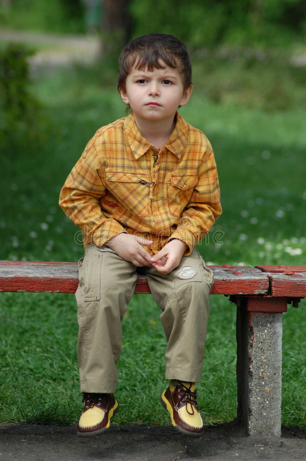 Little boy waiting on a bench stock photography