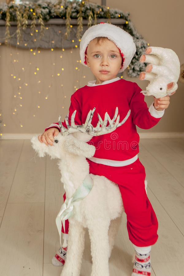 A little boy is waiting for christmas and having fun. the boy is riding a toy deer for Christmas royalty free stock photos