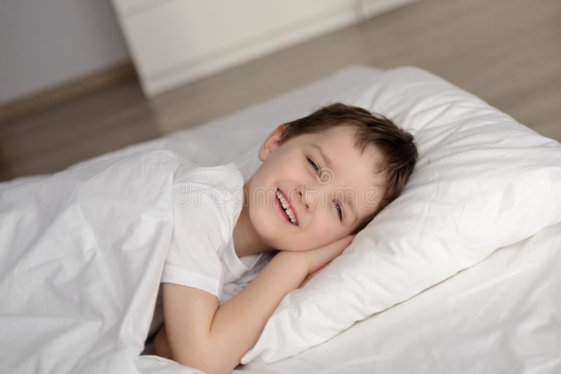 Little boy waking up in white bed with eyes open stock photo