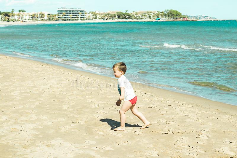 Little boy walking along the beach stock images