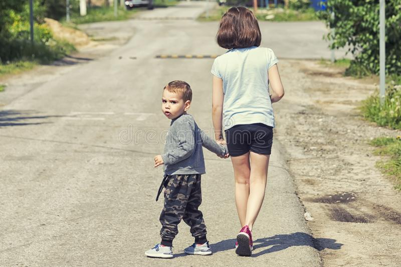 The little boy is walking along the road with his sister. A little boy is walking along the road with his sister, walking along the roadway stock image