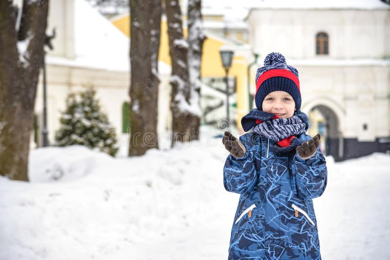 Little boy walking in the park. Child going for a walk after school with a school bag in winter. Children activity outdoors in royalty free stock photography