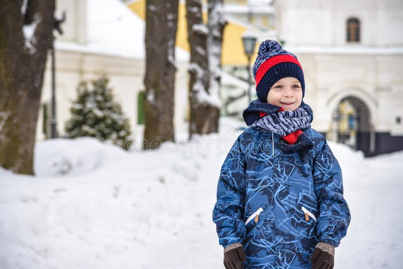 Little boy walking in the park. Child going for a walk after school with a school bag in winter. Children activity outdoors in royalty free stock photo