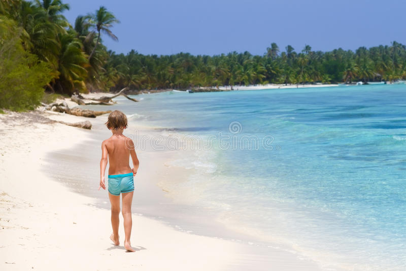 Little boy walking on tropical beach stock photography