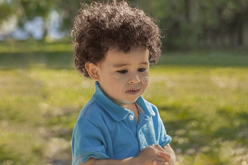 A little boy walks alone with a concerned expression looking down royalty free stock photo