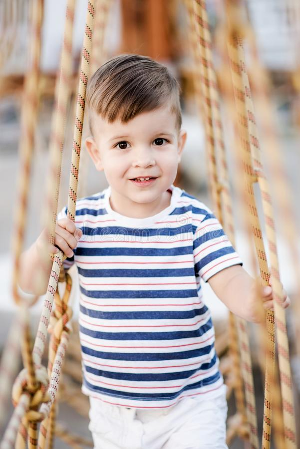 A little boy walks along a stretched wooden bridge in a rope town royalty free stock photography