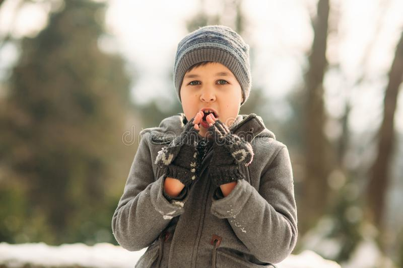 Little boy warming his hands. Winter weather. Snow around royalty free stock image