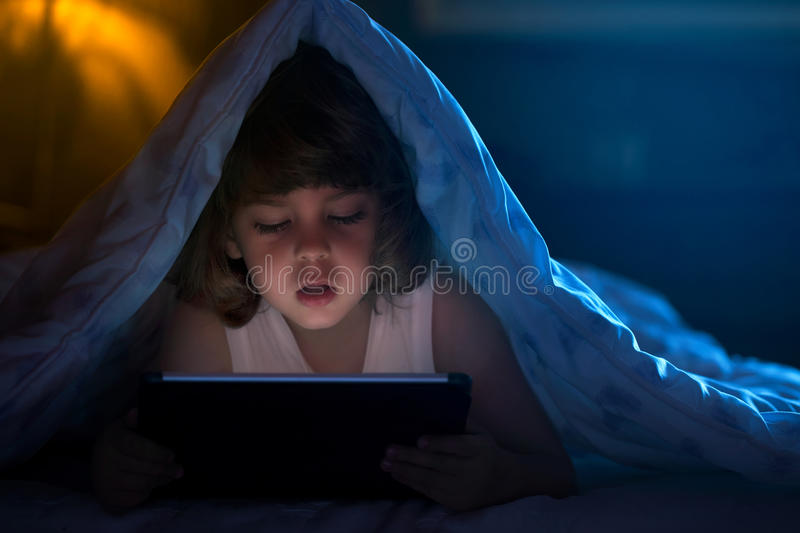 Little boy watching cartoons at night royalty free stock images