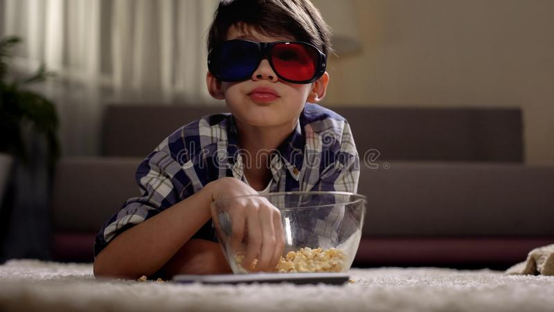 Little boy watching movies in 3d glasses and eating popcorn, enjoying at home. Stock photo royalty free stock images