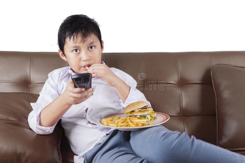 Little boy watching tv while enjoying fast food stock photography