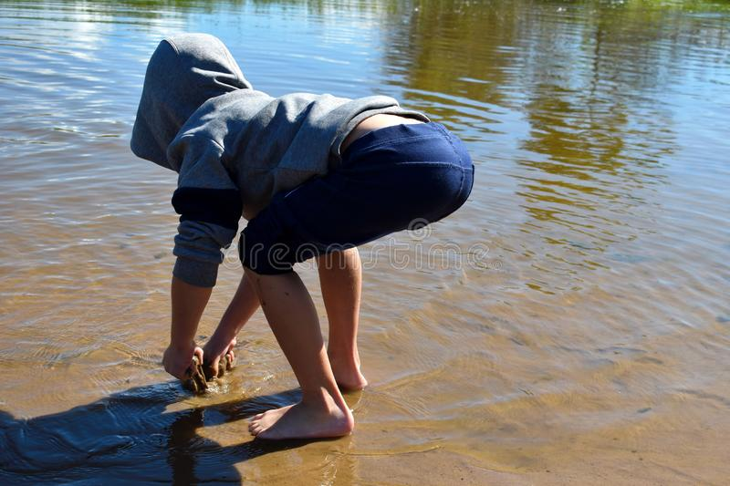 Little boy in water in lake. Child in clothes costs knee-deep in river royalty free stock photography