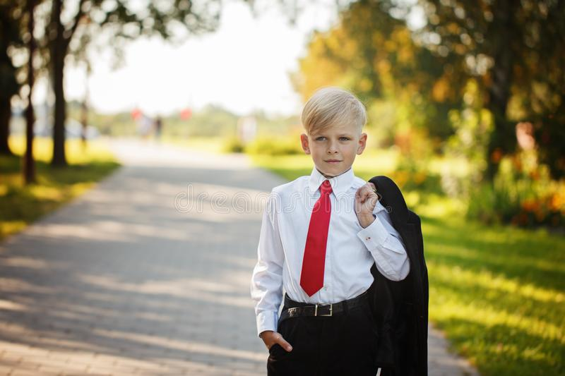 Little boy wearing business suit and red tie on nature background royalty free stock images